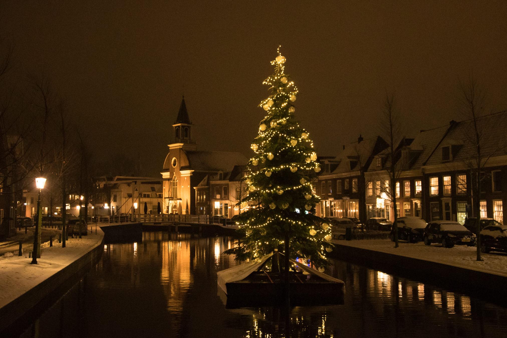 De Oudegracht in Weesp met sneeuw en kerstboom op ponton.