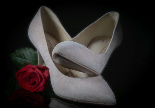 Foto van de schoenen van de bruid met roos